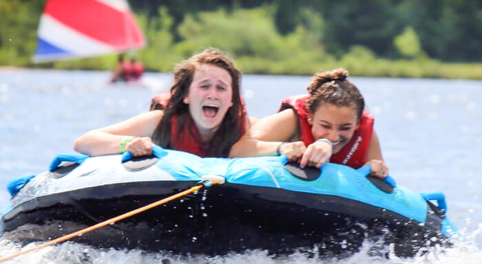 Campers tubing on lake