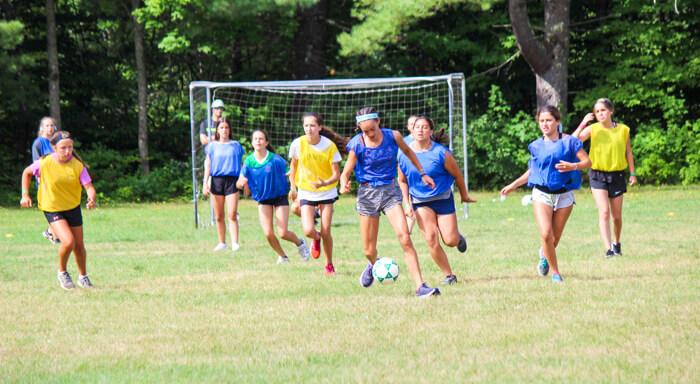 Girls play soccer at summer camp
