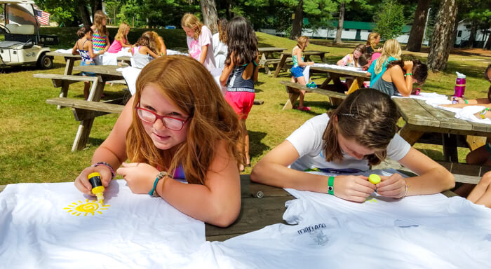 Campers use paint to decorate shirts