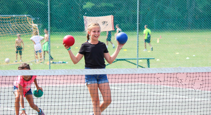 Girl holds two dodgeballs during summer camp game