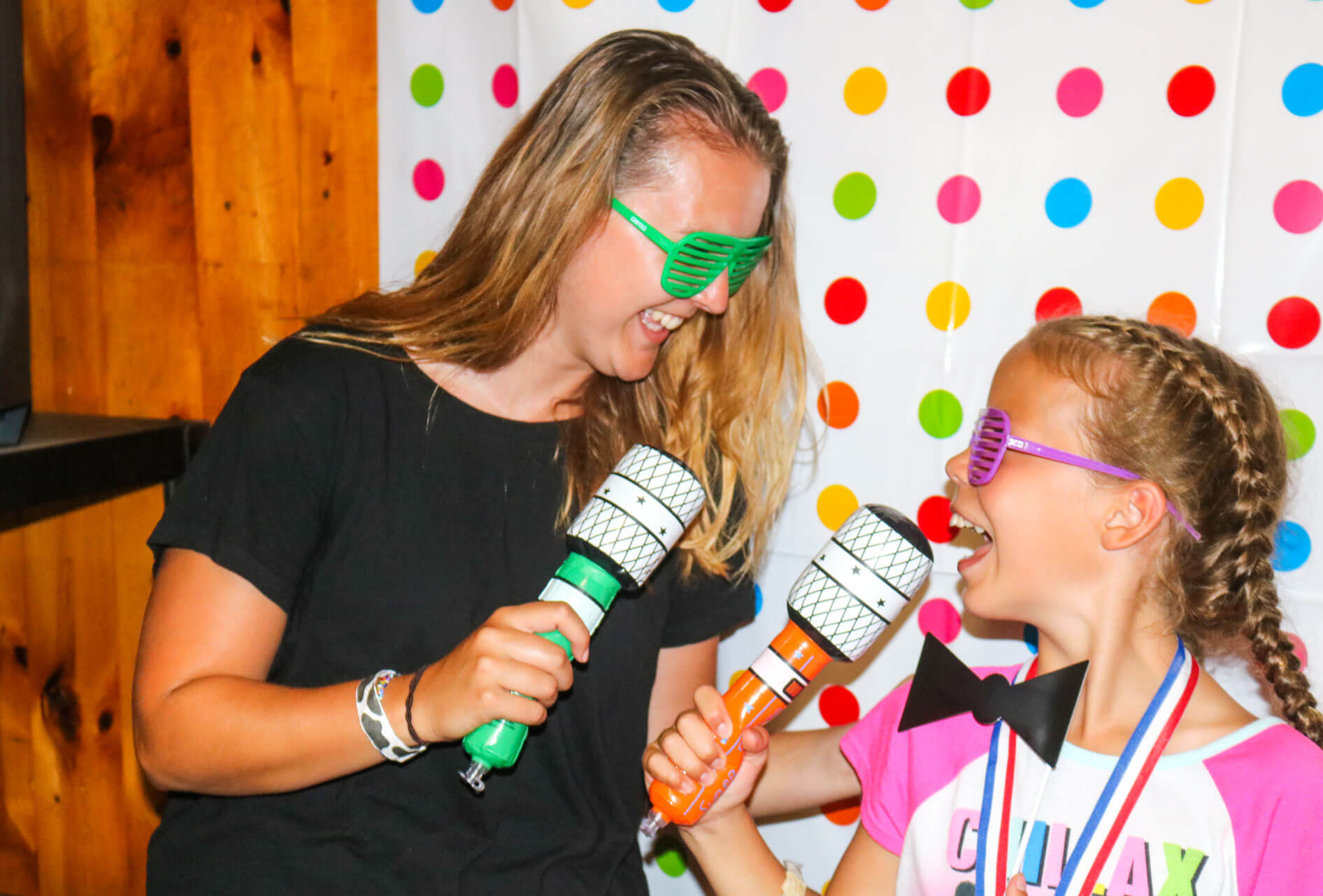 Counselor and camper sing into colorful microphones