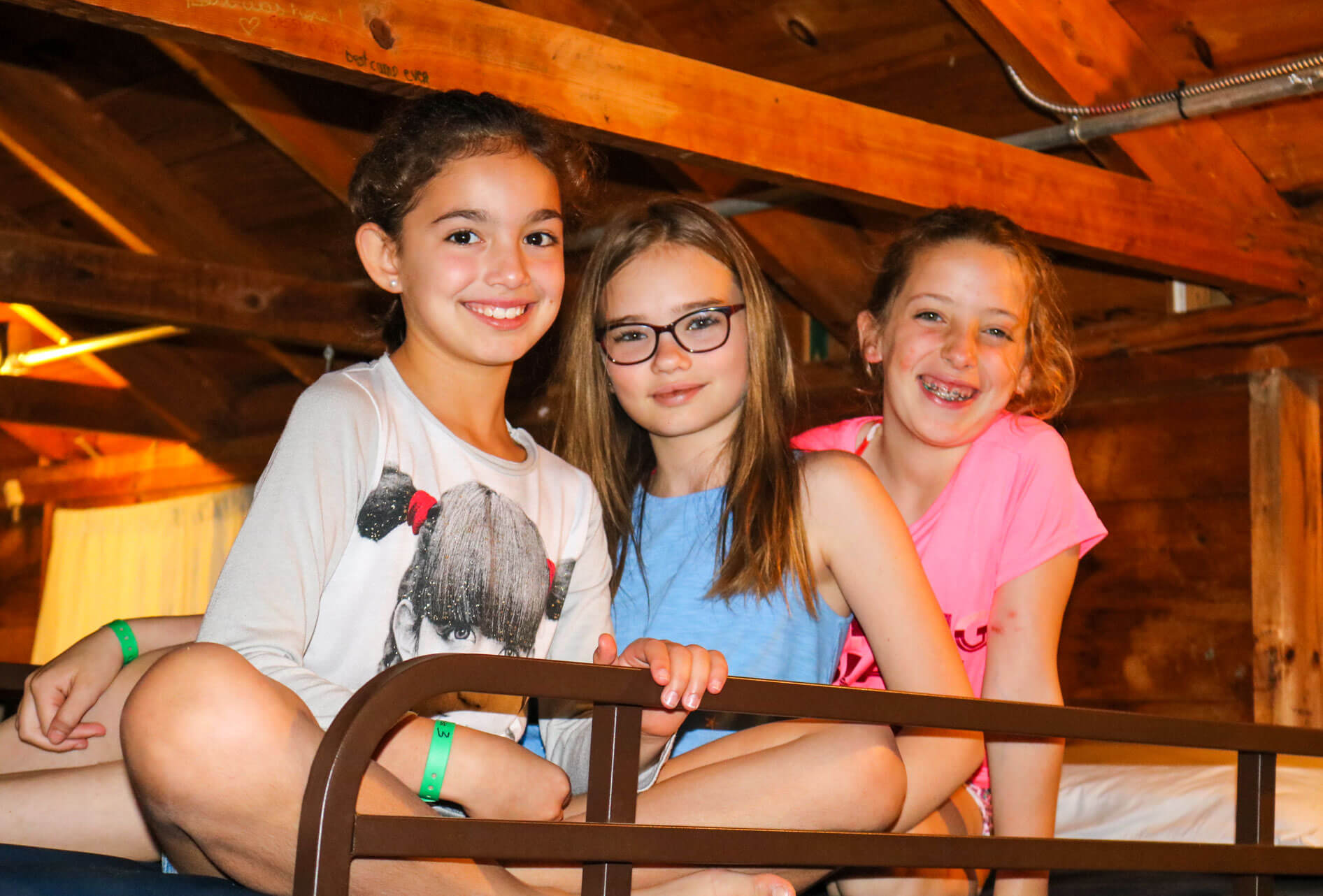 Three young girls sit on camp cabin bunk