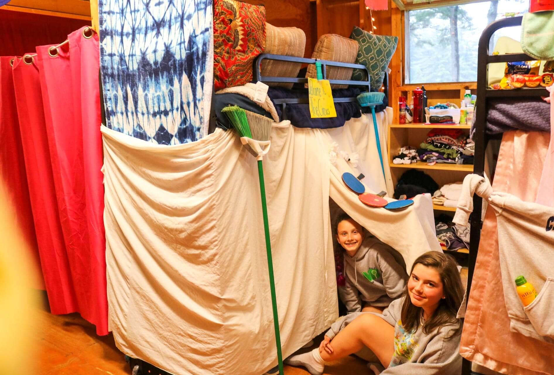 Girls sit in blanket fort in camp cabin