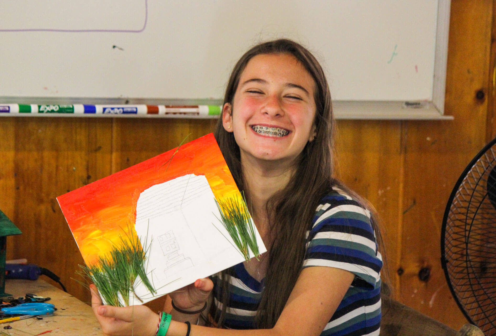 Smiling camper holds up painting