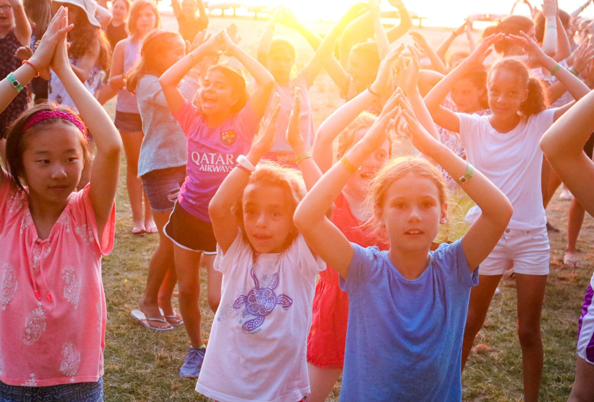 Group of campers dance with sunset behind them