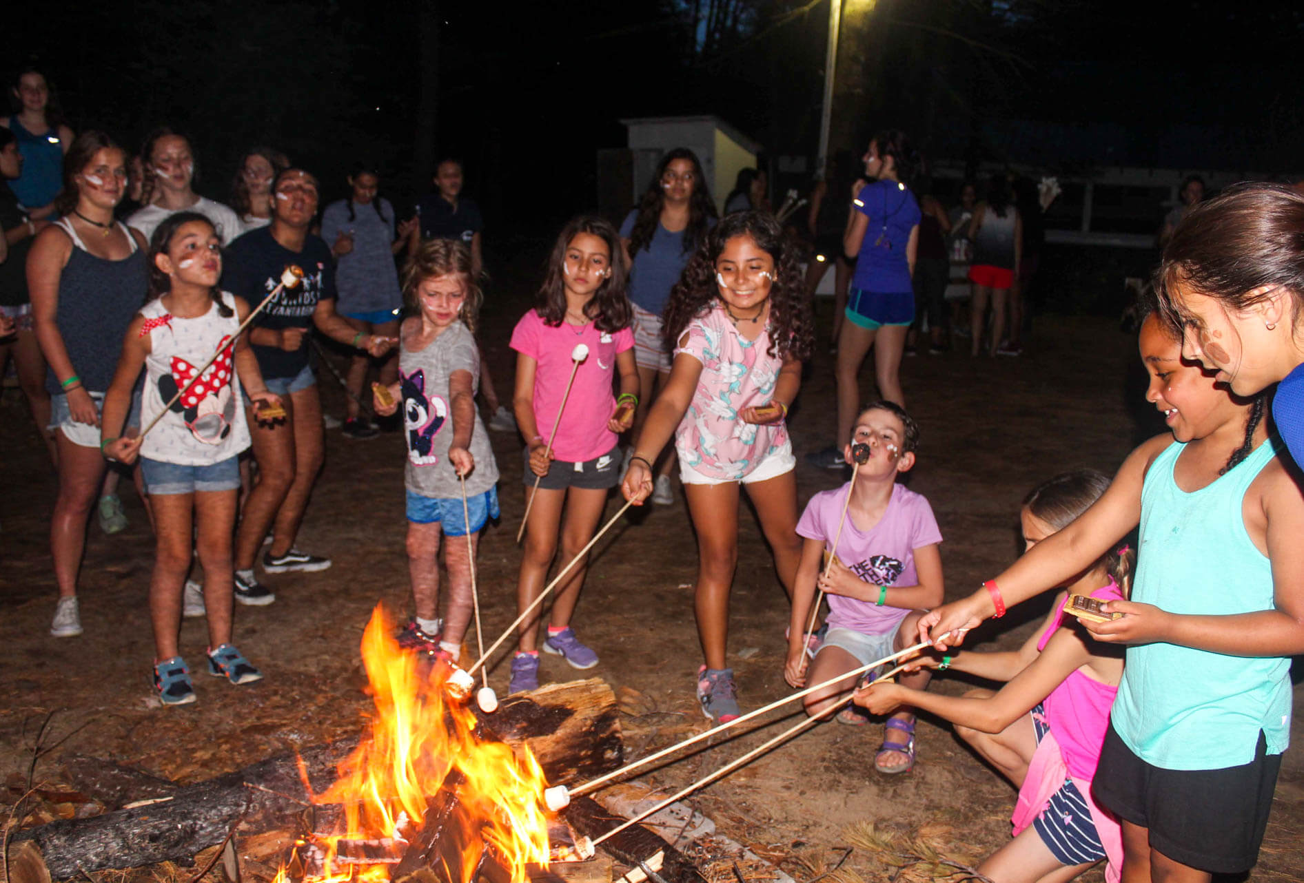Campers roast marshmallows over fire