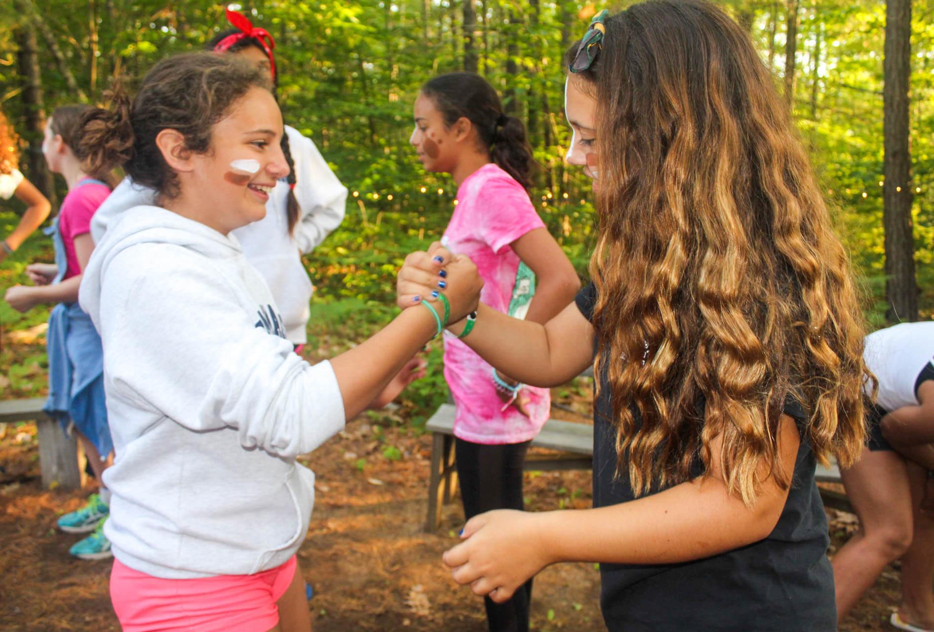 Two campers perform handshake