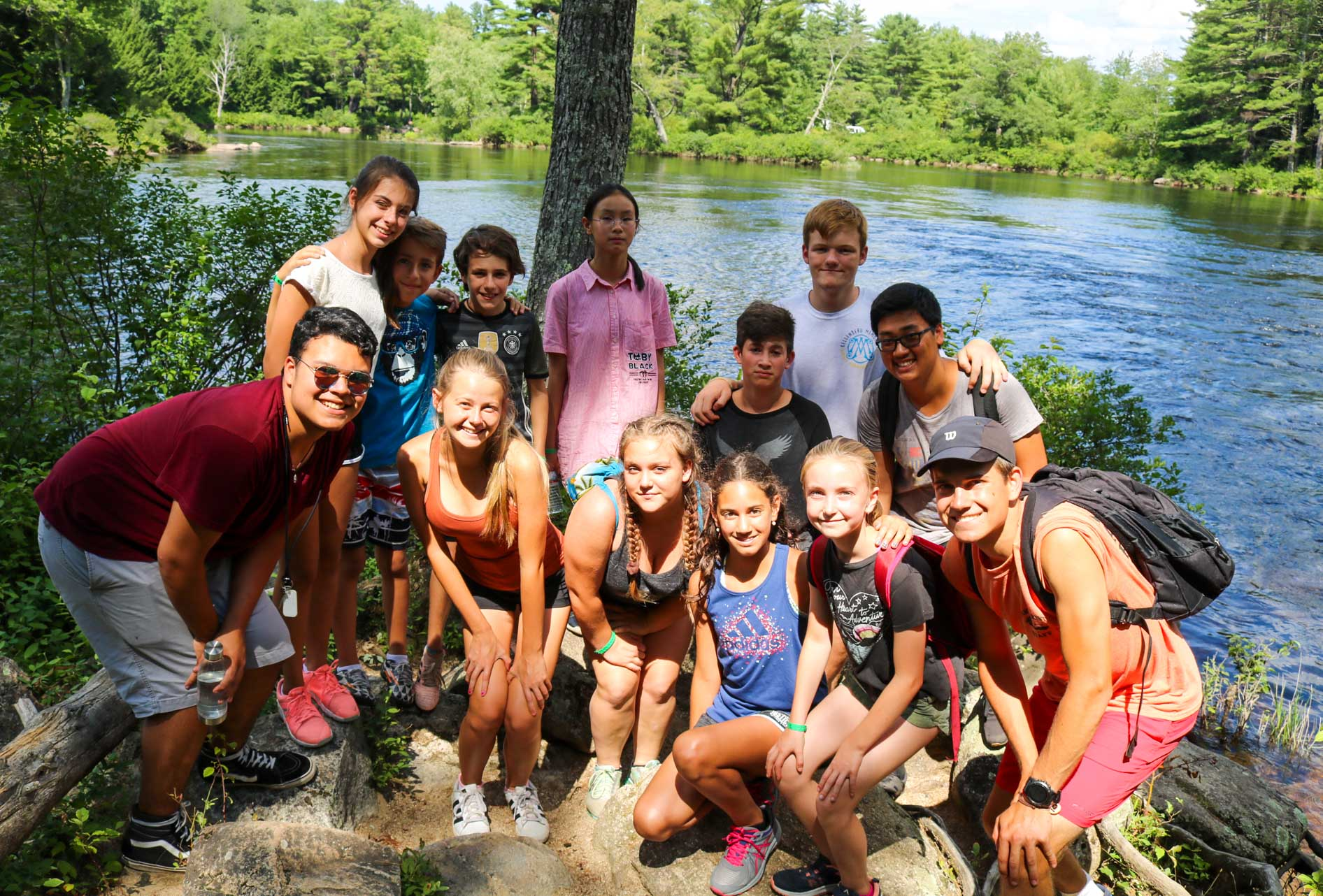 Camp hiking group poses for photo near lake