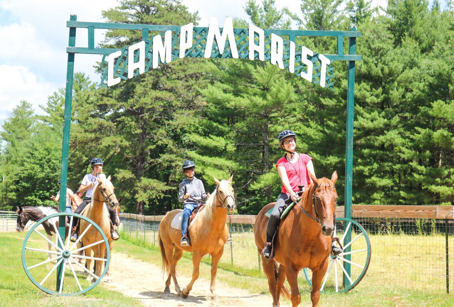 Horseback riding group passes Camp Marist sign