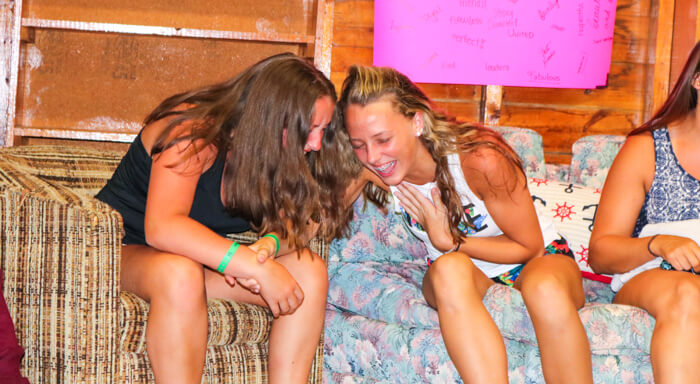 Girls laugh together in camp cabin