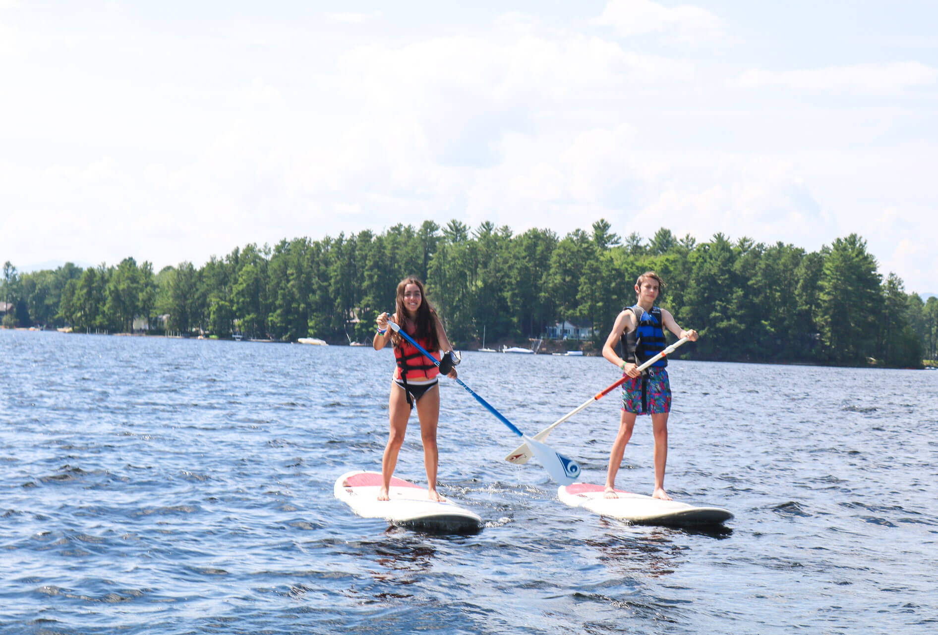 Campers paddle stand-up paddleboards
