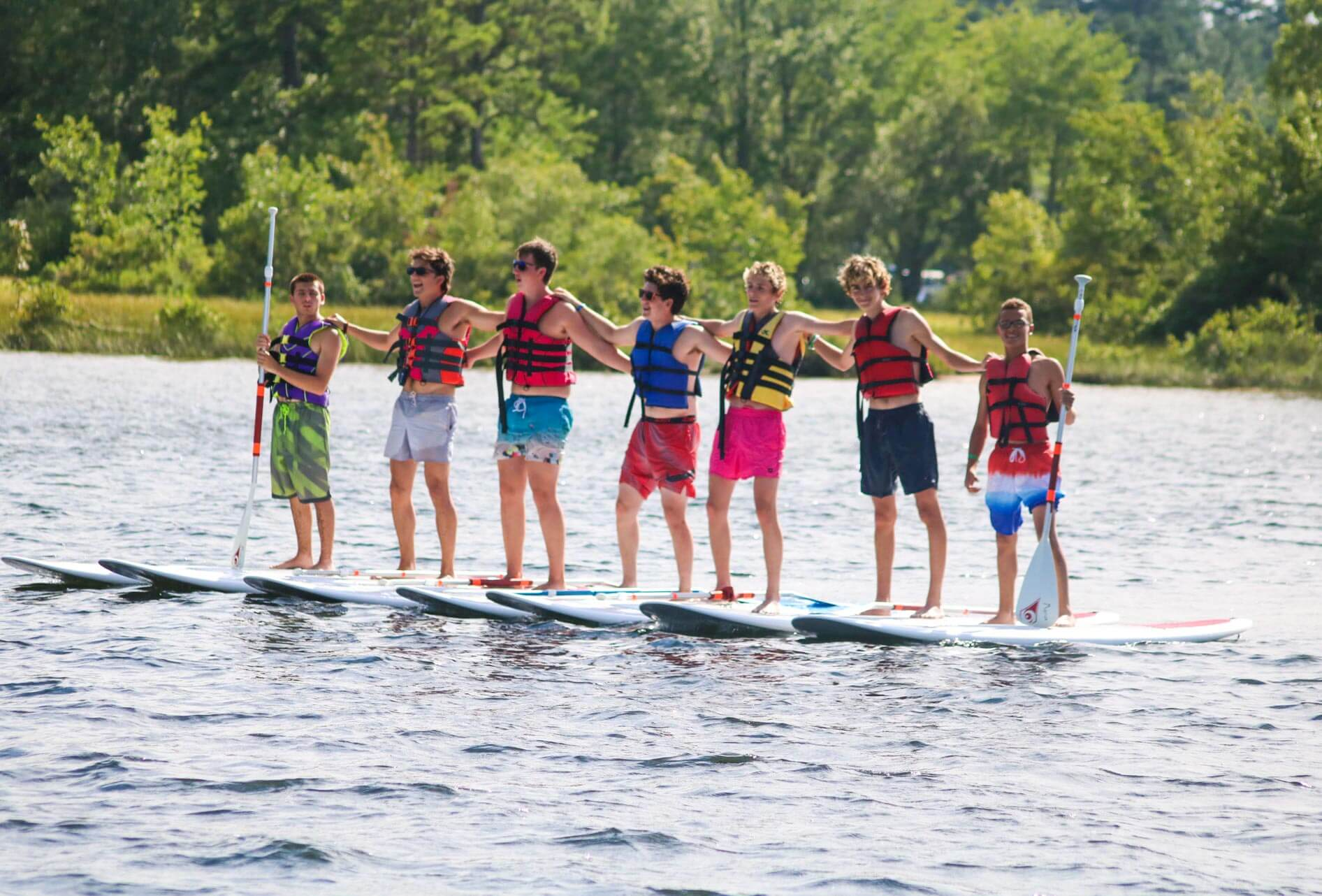 Row of campers on stand-up paddleboards