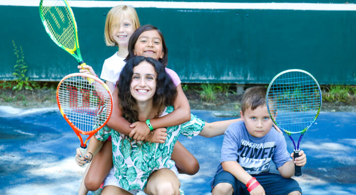 Campers and counselor with tennis racquets