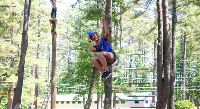 Camper ziplines through trees