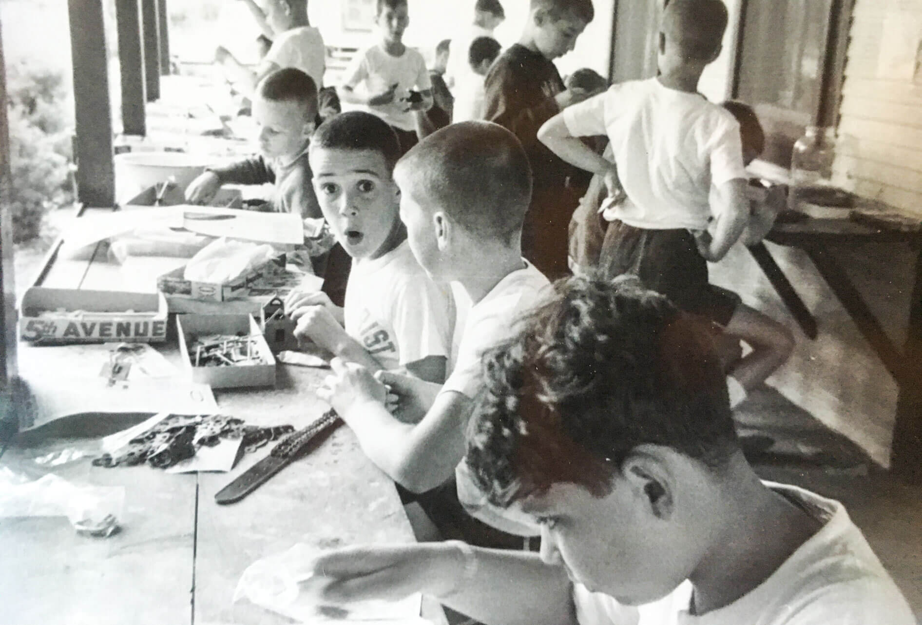 Black and white photo of campers doing crafts