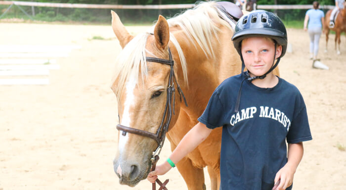 Camper stands next to horse in corral