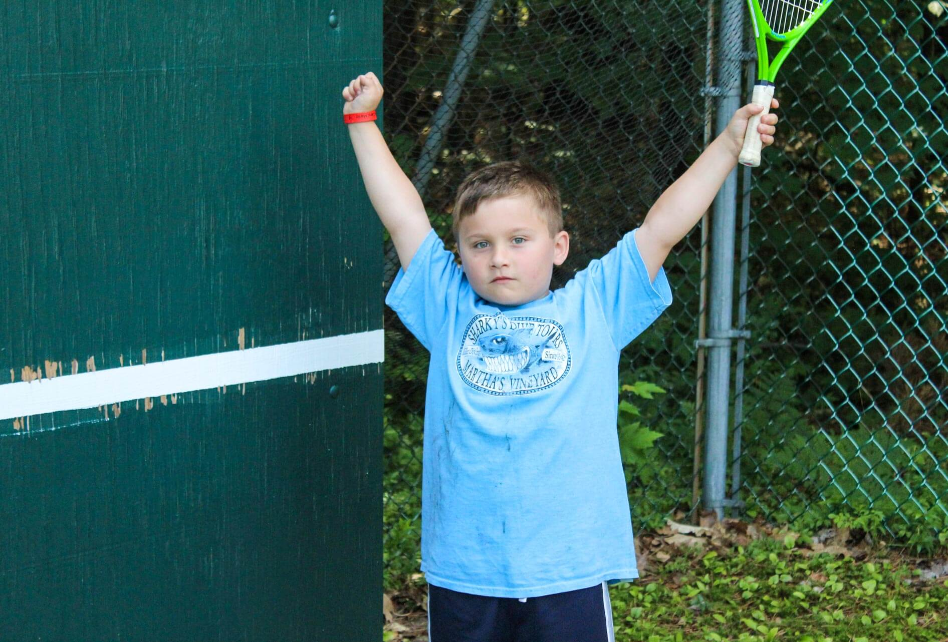 Young camper stretches while holding tennis racquet