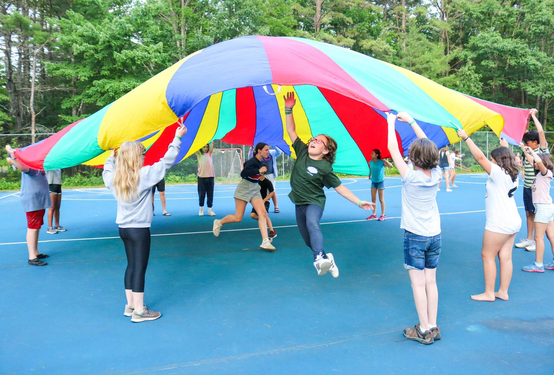 Young campers do activity with large colorful fabric