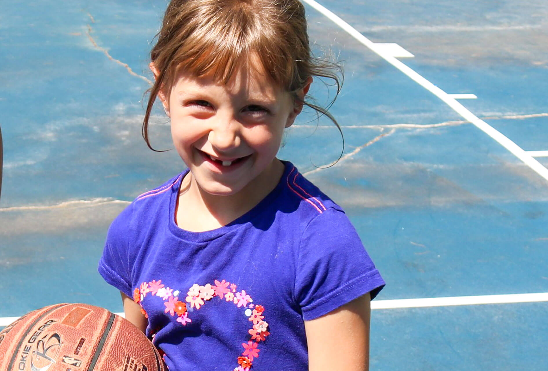 Smiling young camper holds basketball