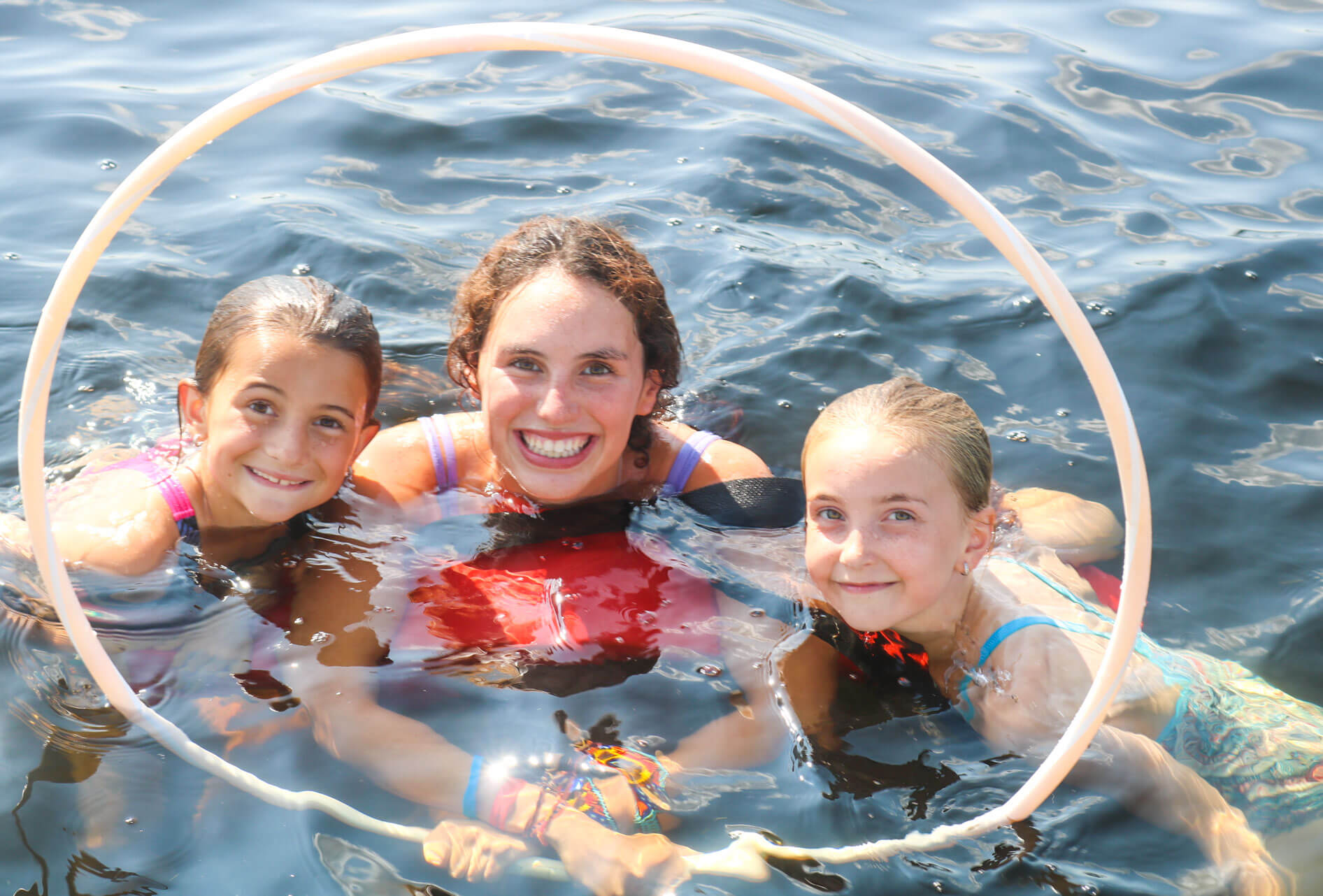 Two campers and counselor float in water