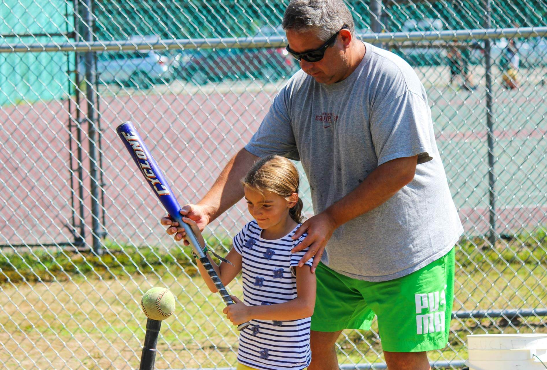 Staff helps young camper with softball