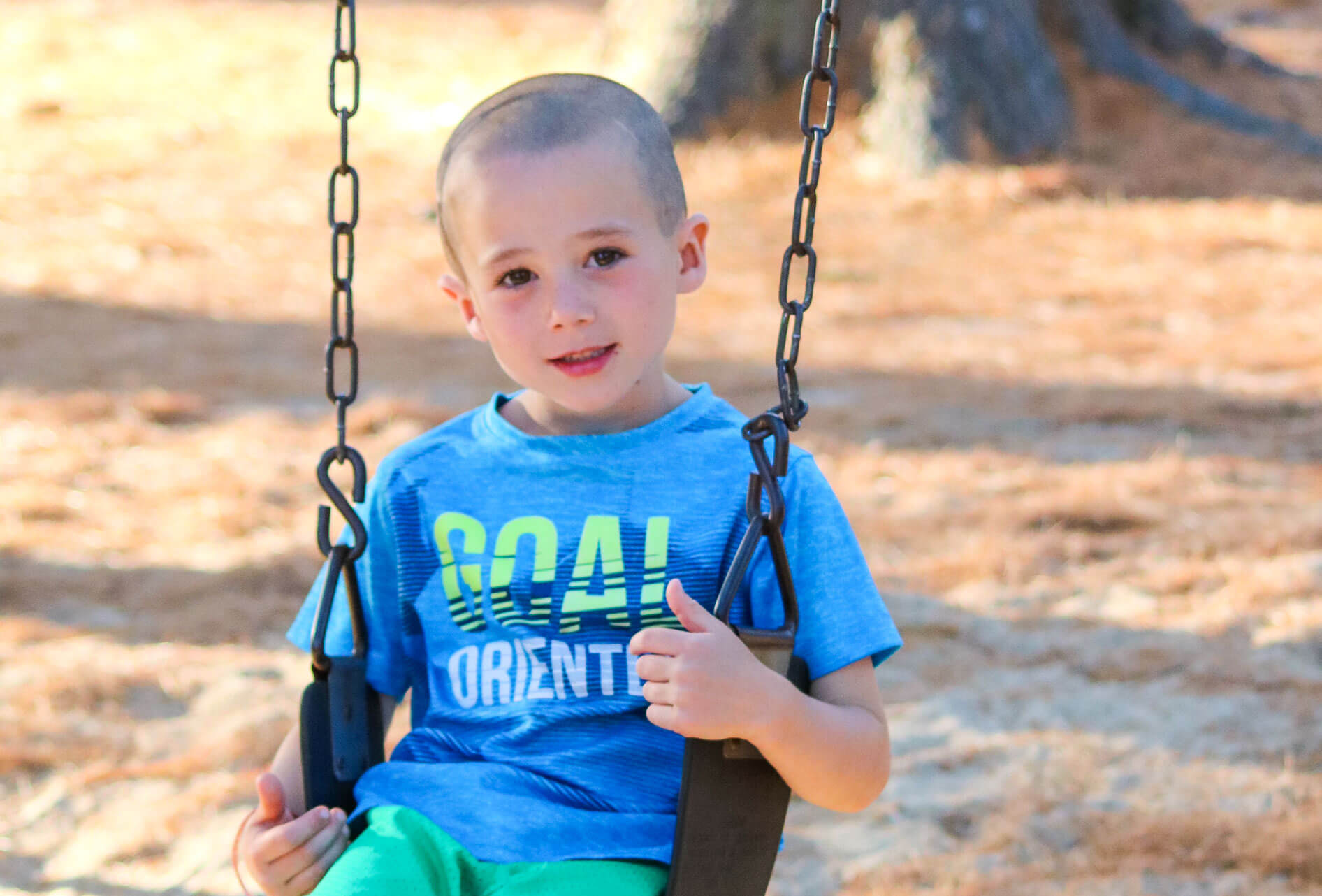 Young camper sits on swing