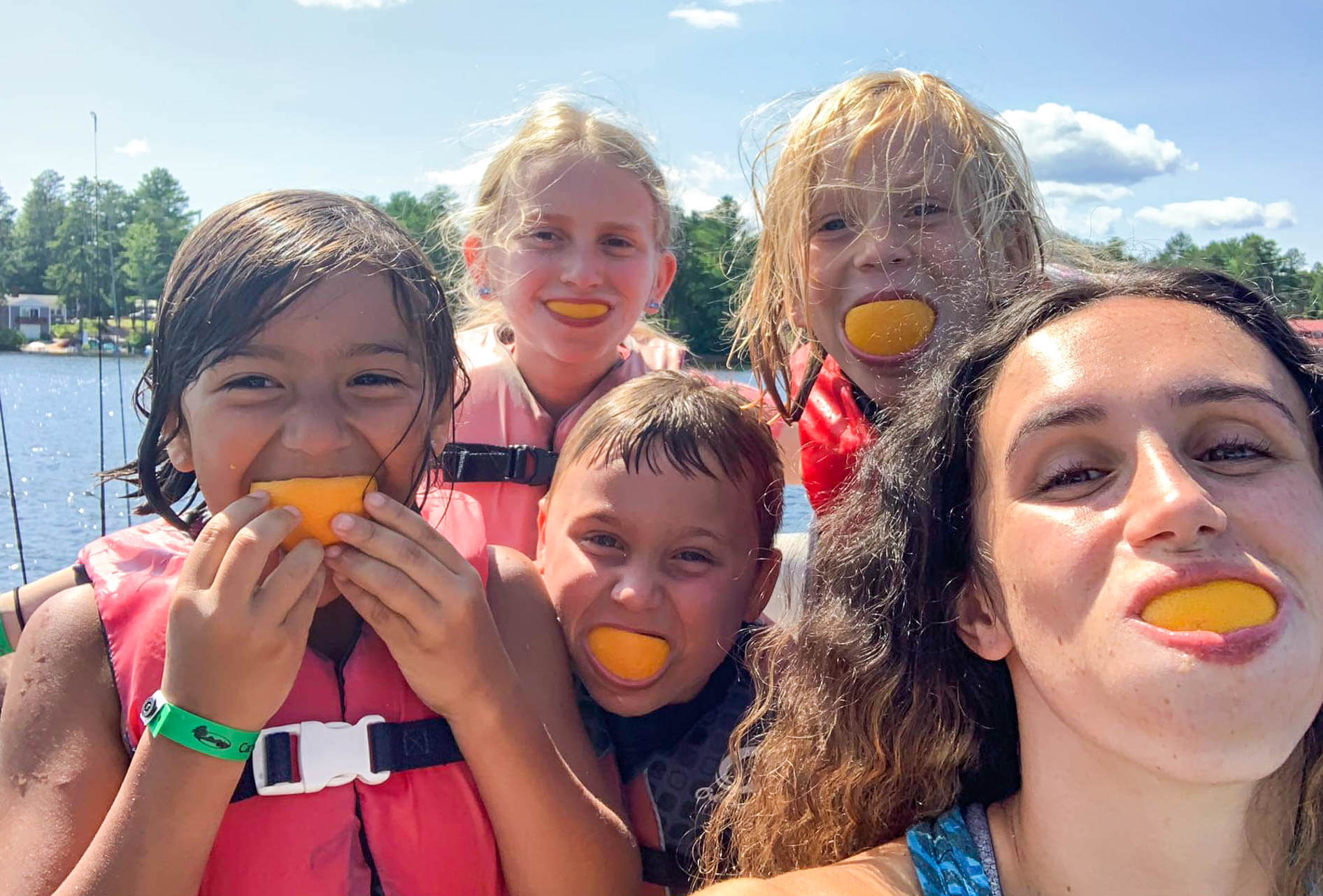 Campers hold orange slices in their mouths