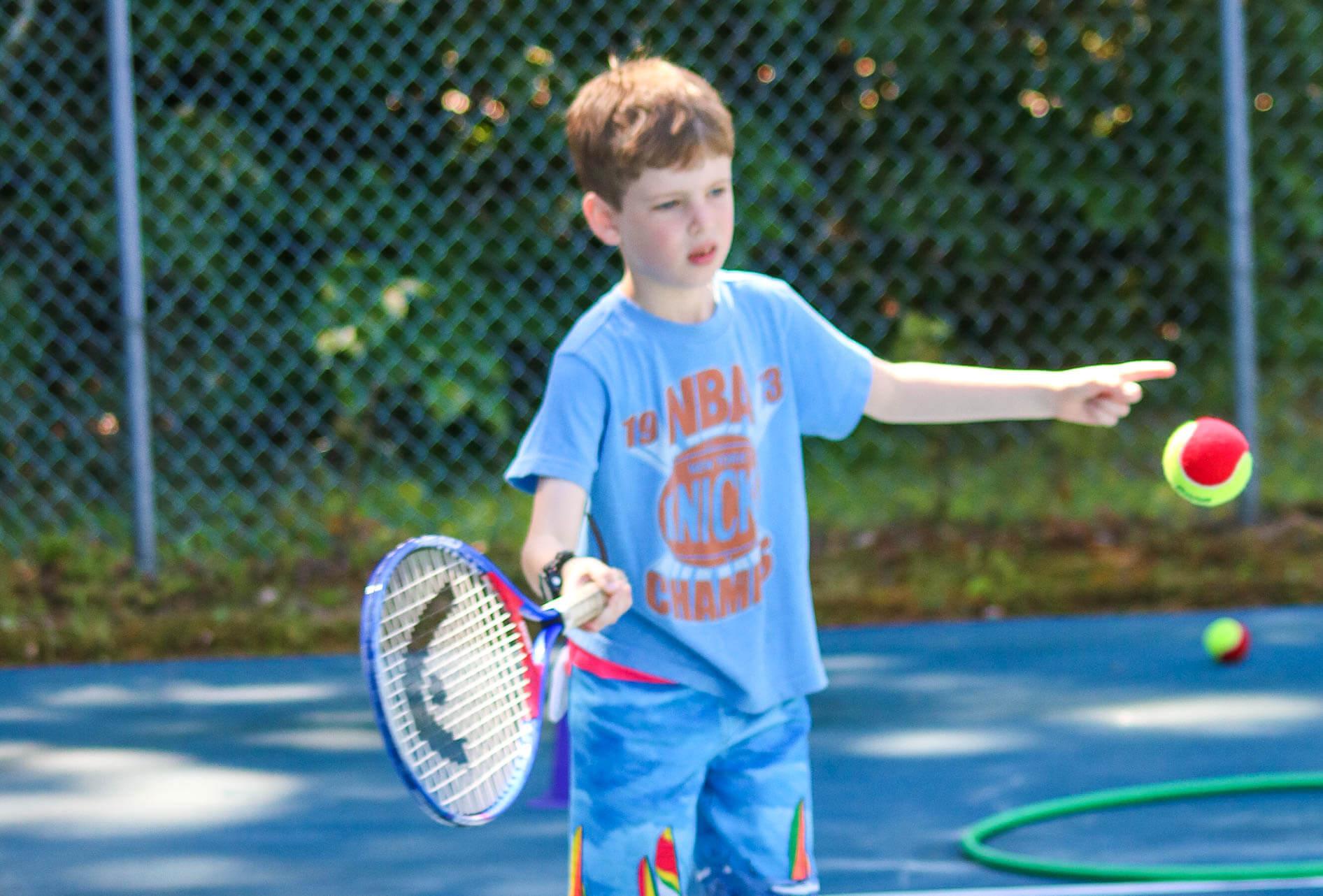 Young camper swings tennis racquet