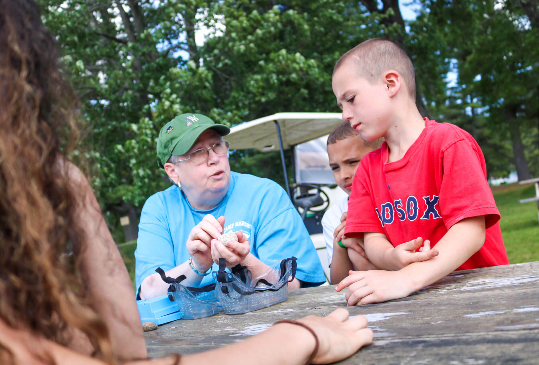 Staff helps young camper with project