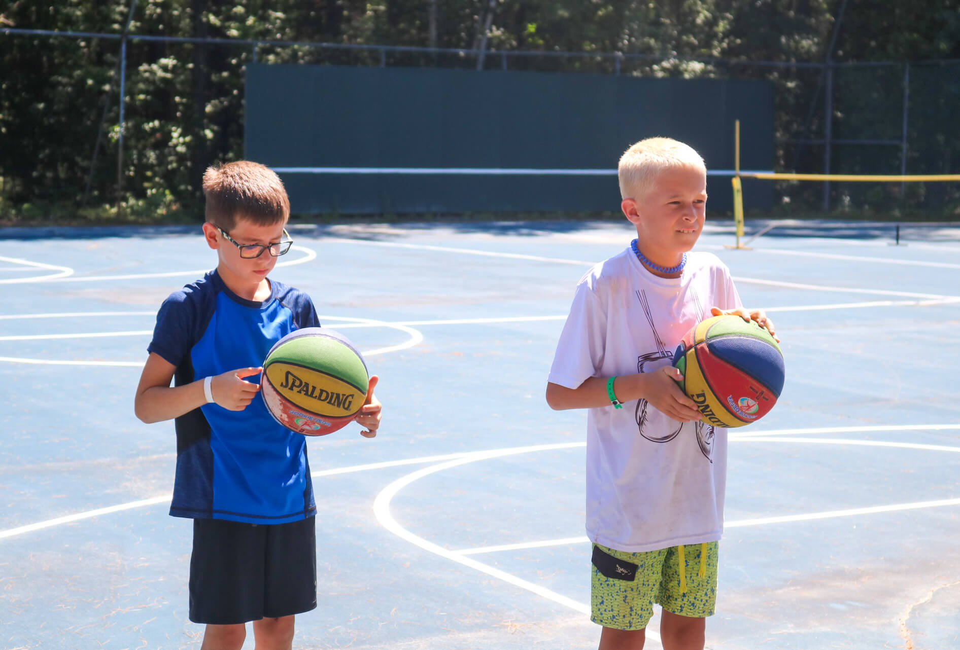 Two young campers hold colored basketballs