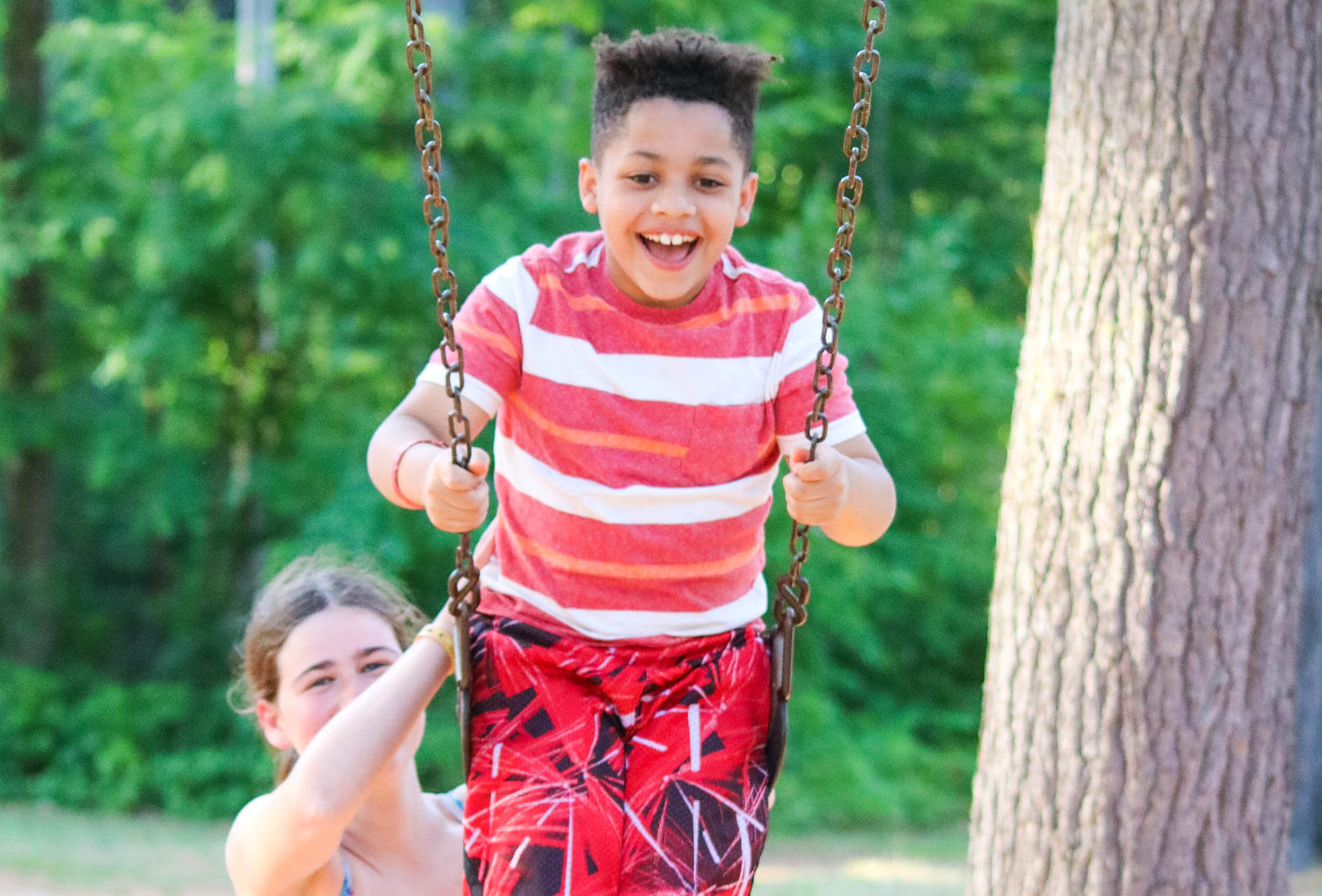 Counselor pushes young camper on swing